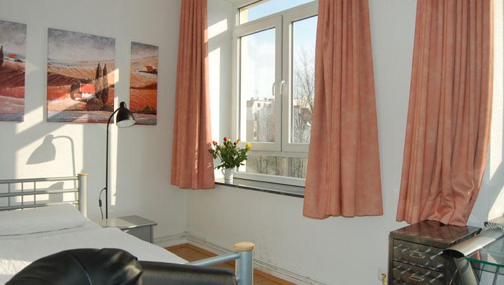 Raum mit Bett, Lampe, Gardinen, Bilder über dem Bett und Lichteinfall durchs Fenster
