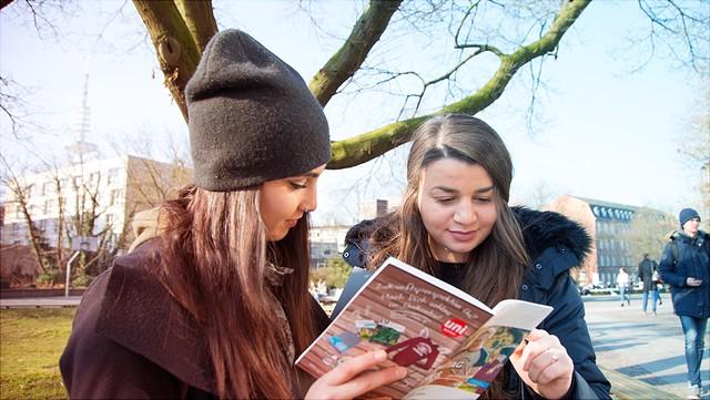 Zwei Studentinnen schauen in eine Unitag-Broschüre