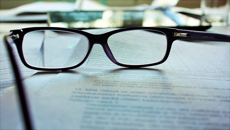 Brille liegt auf beschriftetem Papier