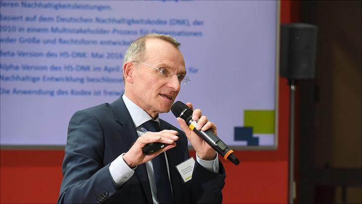 Prof. Alexander Bassen mit Mikrofon in der Hand erläutert den Hochschul-DNK