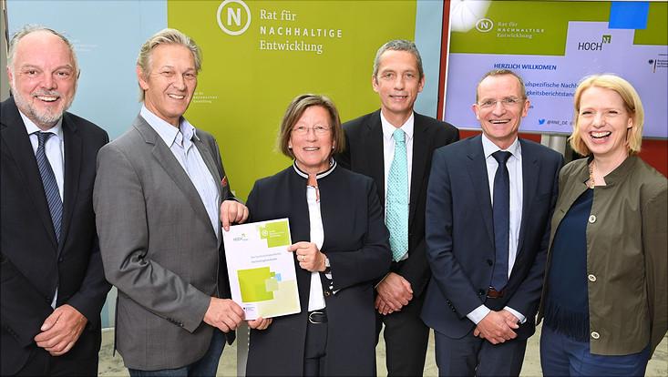 Foto mit sechs Personen, von denen zwei die Broschüre zum Hochschul-Nachhaltigkeitskodex in die Kamera halten und vor Bilderwand des Rats für nachhaltige Entwicklung sowie HOCH-N stehen.