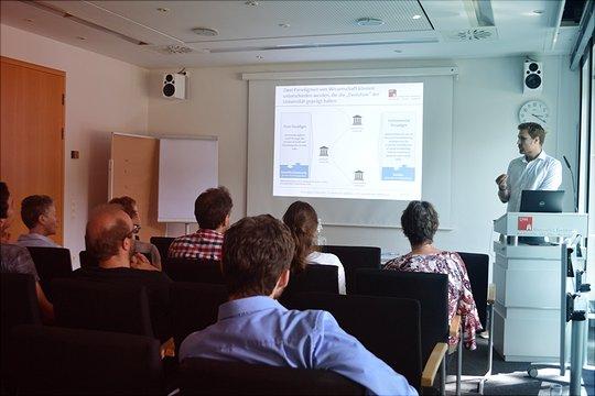 Eine männliche Person hält einen Vortrag und hat dazu eine Powerpoint-Präsentation im Hintergrund vorbereitet.