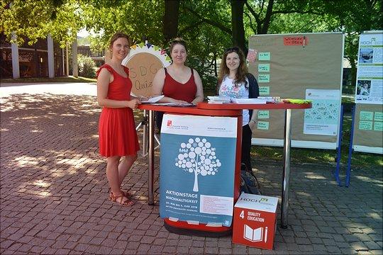 Der Aktionsstand hinter dem drei Studierende stehen, die mit Infomaterial über die SDGs informieren.