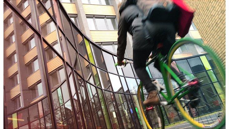 Ein grünes Fahrrad auf dem jemand fährt etwas unscharf fotografiert.