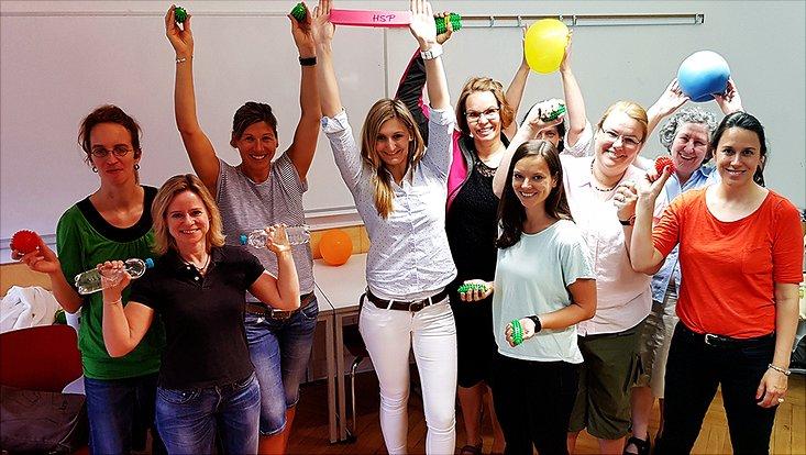 Zehn motivierte Beschäftigte der Uni Hamburg posieren mit allerlei kleinen Sportgeräten