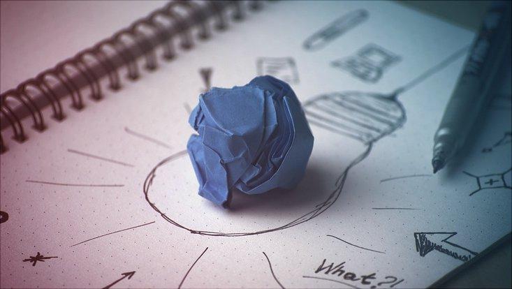Ein weißes Blatt Papier mit einer aufgemalten Glühbirne in der Mitte in der ein zusammengeknülltes blaues Papier liegt. Der Prozess des Brainstorming soll dargestellt werden.