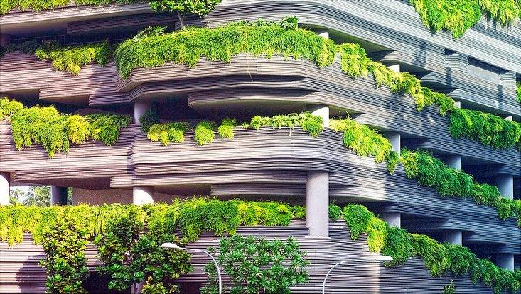Ein graues Haus mit Balkonen aus denen grüne Pflanzen hängen und vornüber nach draußen wachsen.