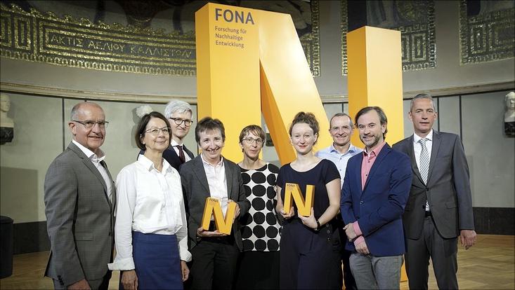 """neun Personen, vier Frauen und fünf Männer, stehen nebeneinander vor einem großen orangenen Buchstaben N auf dem in dunkelgrau """"FONA Forschung für Nachhaltige Entwicklung"""" steht. Zwei Frauen halten ein ebensolches N in klein in den Händen"""