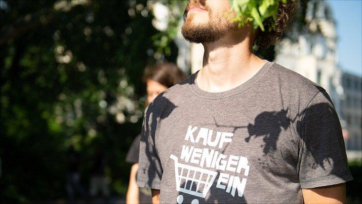 """junger Mann mit rotem Vollbart schaut in den Himmel und trägt T-Shirt mit Aufschrift """"Kauf weniger ein"""""""
