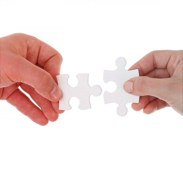 Zwei Hände die jeweils ein Puzzleteil halten nähern sich an.