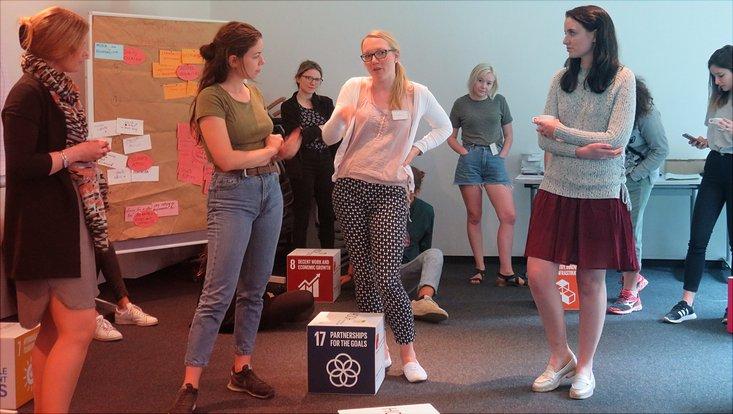Eine Gruppe Studierender steht zusammen und diskutiert.
