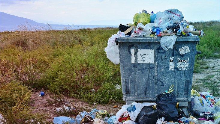 Eine Mülltonne quilt über vor lauter Müll.