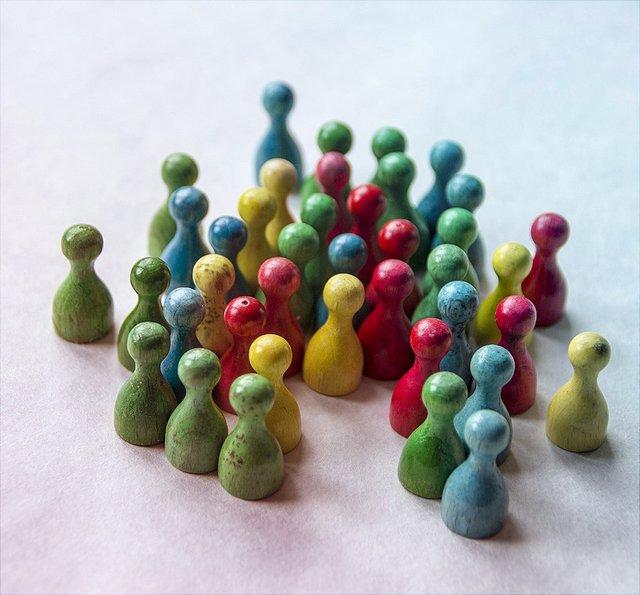 Verschiedenfarbige Spielfiguren aus Holz stehen zusammen.