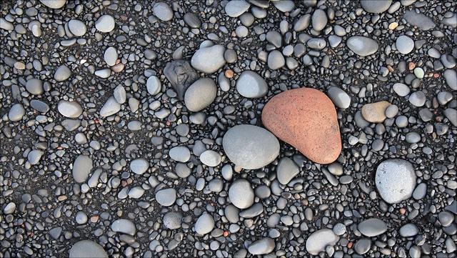 graue Kiesel, in der Mitte ein großer roter runder Stein