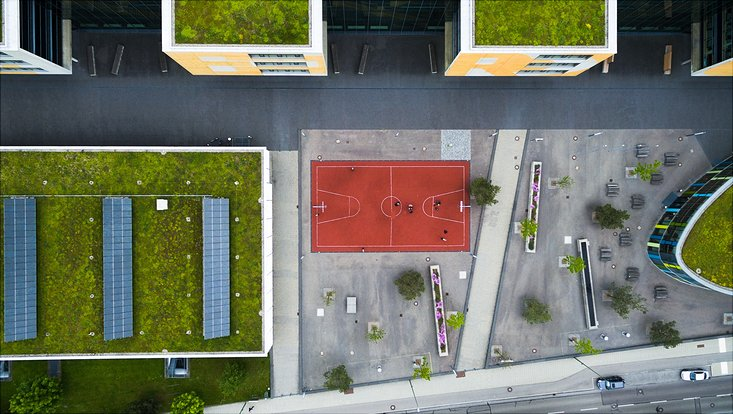 Blick von oben auf Gebäude-Ensemble mit Solaranlage und Gründächern