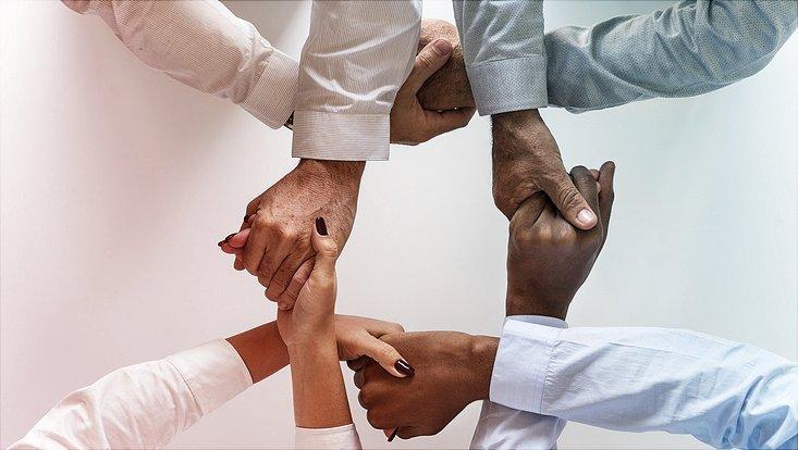 Vier Menschen halten sich über Kreuz an den Händen und signalisieren so Zusammenhalt.