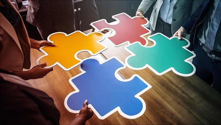 Vier Menschen halten vier verschiedenfarbige Puzzleteile in der Hand die zueinander passen.