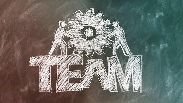 An einer Tafel sind mit Kreide zwei Figuren aufgemalt, die zusammen ein Zahnrad anschieben. Darunter ist das Wort Team geschrieben.