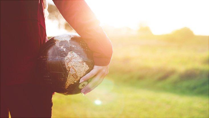 Eine Person hält eine Weltkugel unter dem Arm vor dem Hintergrund einer grünen Wiese.