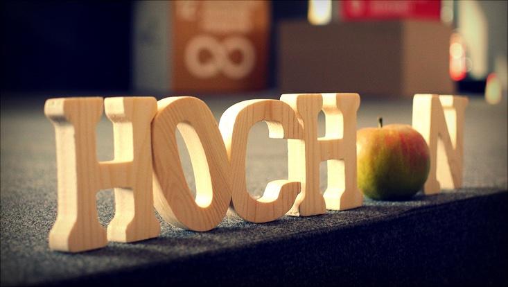 HOCH-N aus dreidimensionalen, aufrechtstehenden Holzbuchstaben, schräg von der Seite fotografiert, das Hoch und das N werden von einem Apfel getrennt