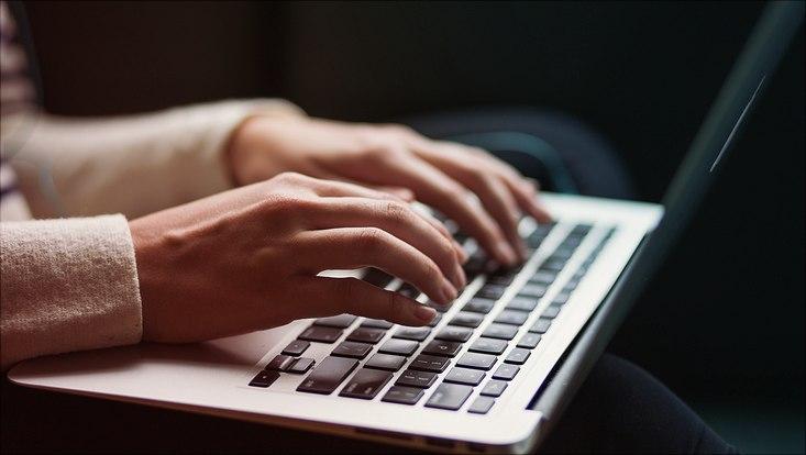 Person schreibt auf einem Laptop