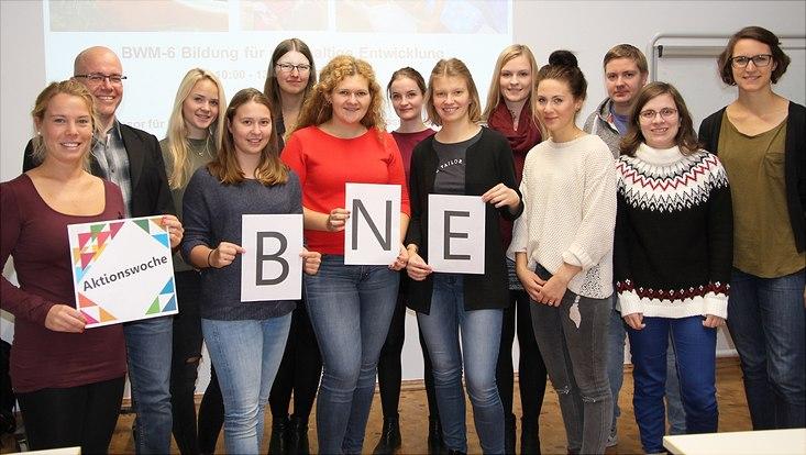 """eine Gruppe Student*innen und Lehrende die drei Blätter hochhalten. Auf dem einen steht """"Aktionswoche"""", auf den drei anderen die Buchstaben B,N und E"""