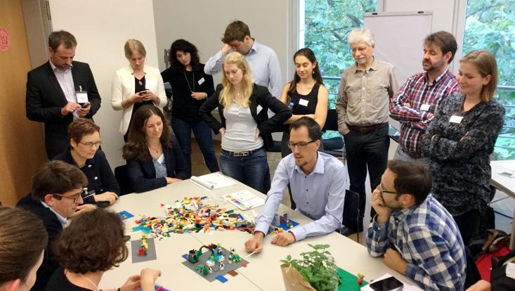 Gruppe Menschen um einen Tisch, einige sitzen andere stehen, in der Mitte Lego mit welchem gearbeitet wird