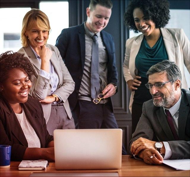 Menschengruppe vor Computer im Gespräch