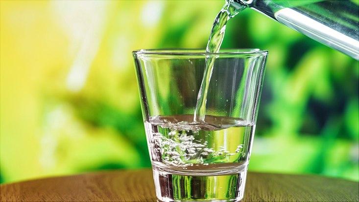Wasserglas vor grünem Hintergrund