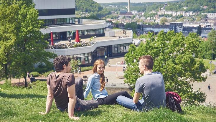 Drei Studierende sitzen auf einem Hügel auf der Wiese, im Hintergrund ist ein Universitätsgebäude zu sehen