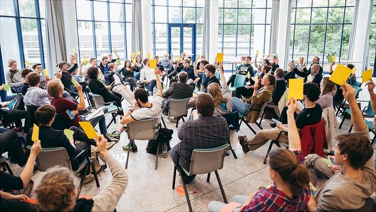 Gruppe Menschen in einem gläsernen Gebäude, sitzend von hinten fotografiert, einige heben den die Hand mit einer Abstimmungskarte