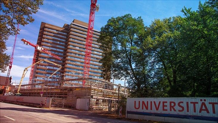 """Eine Baustelle vor der ein Banner mit der Aufschrift """"Universität"""" zu sehen ist."""