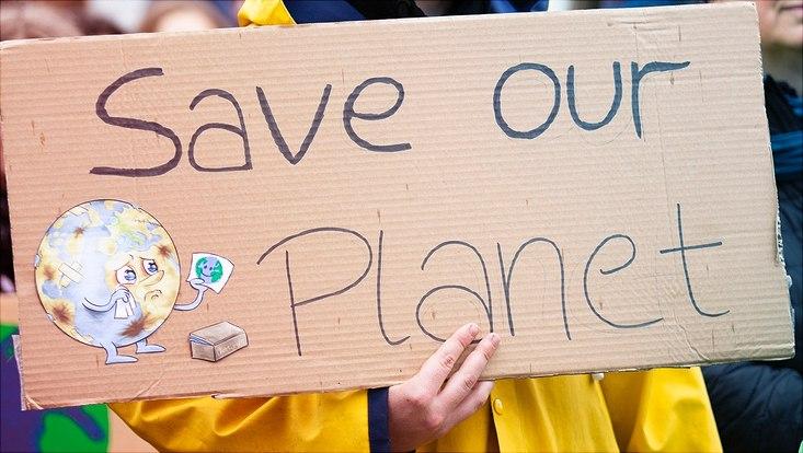 """Ein Plakat mit der Aufschrift """"Save our Planet"""" wird hochgehalten."""