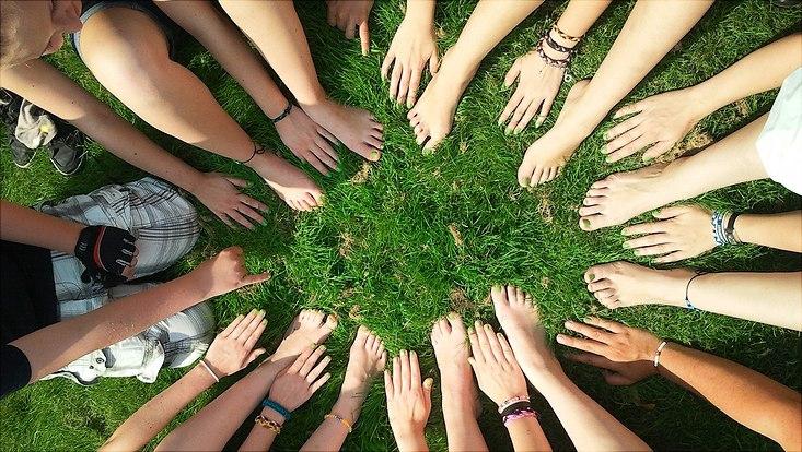 Viele Füße und Hände bilden einen Kreis auf einer Rasenfläche
