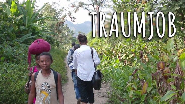 Menschen laufen auf schmalem Pfad durch den Dschungel