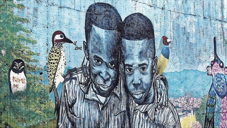 Buntes Wandgraffitti mit zwei Menschen und Papageien