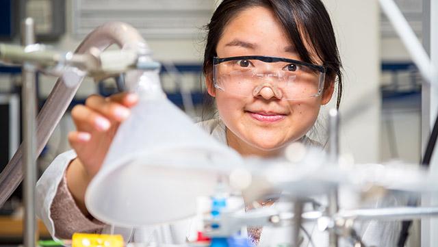 Studentin mit Schutzbrille im Labor sieht freundlich direkt in Kamera