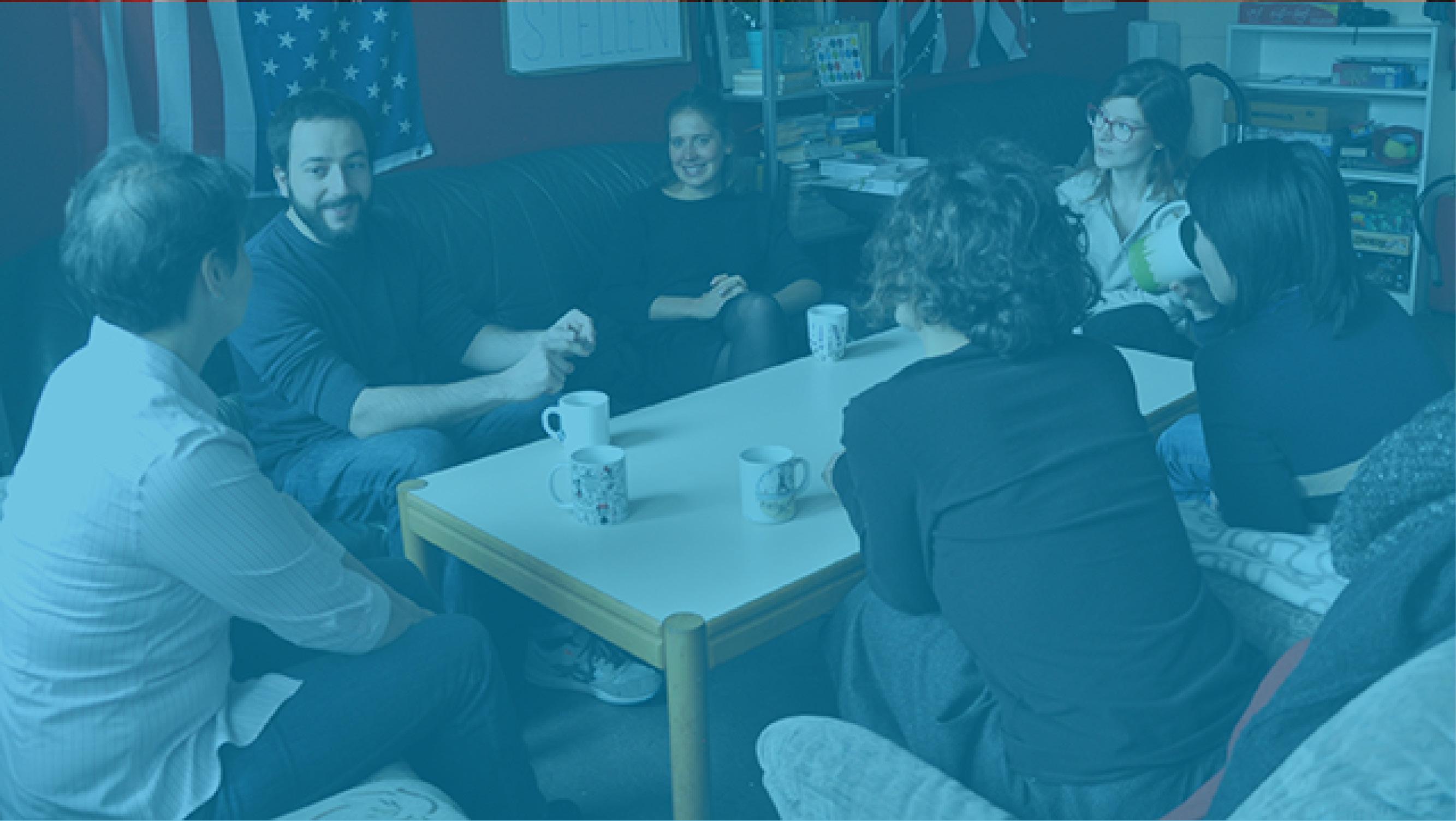 Studierende und Lehrende unterhalten sich im Anglarium bei Kaffee