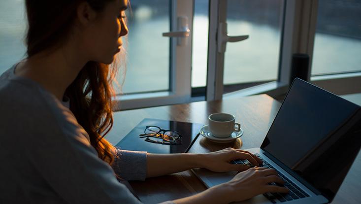Arbeitende Studentin in der Dämmerung vor einem Laptop