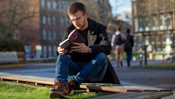 Ein lesender Studierender auf dem Campus der Universität Hamburg