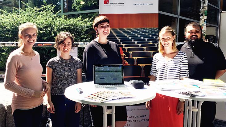 Fünf lächelnde Studierende des Universitätskollegs in der Sonne, in Richtung Objekt blickend, im Hintergrund Informationstafeln