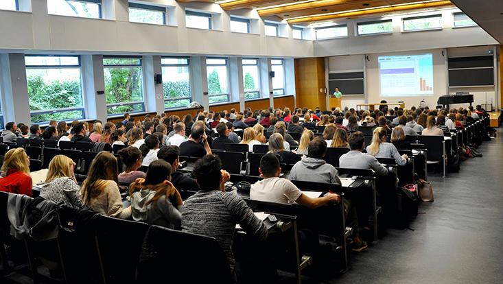 Cover des Kolleg-Boten 75: Viele Studierende sind von hinten zu sehen, sitzend in einer Vorlesung der Vorkurse BWL