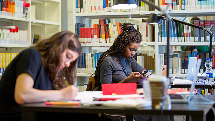 Zwei Studierende in der Bibliothek, lesend