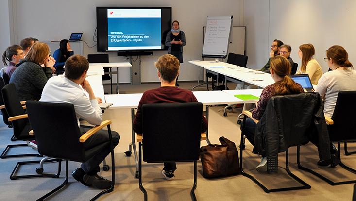 Gruppe an Lehrenden im Seminarraum, Manuela Kenter steht vor ihnen und erklärt etwas