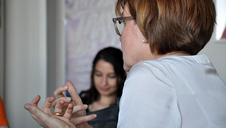 Kursleitende mit Handgeste im Profil, im Hintergrund unscharf der Seminarraum und eine Studierende