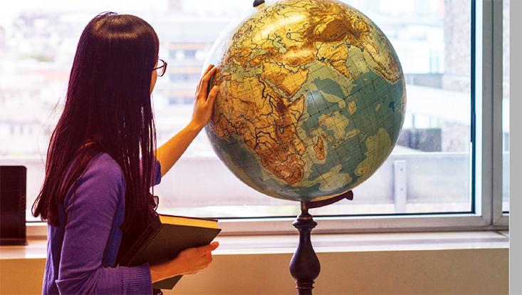 Studierende steht mit Rücken zur Kamera und legt linke Hand an Globus, in der rechten hält sie ein Buch