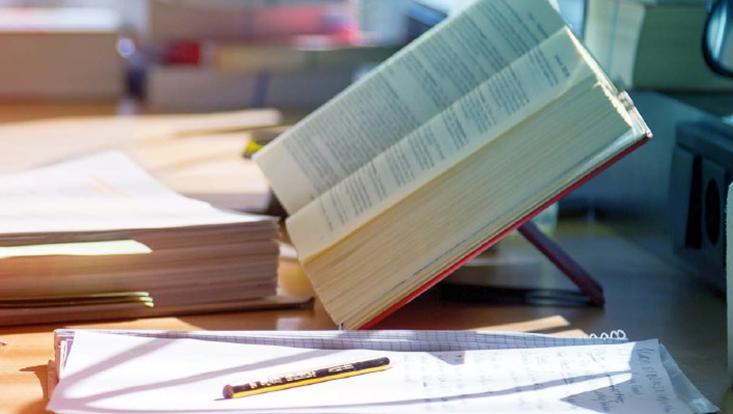 Coverfoto von Band 26 - aufgeschlagenes dickes Buch, davor Block mit Notizen und Bleistift