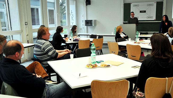 Verschiedene Lehrende sitzend an Schreibtischen, im Hintergrund eine Tafel, an der zwei Vortragende stehen und etwas erklären