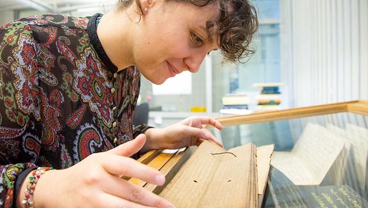 Studierende, die über Manuskript lehnt, lächelnd