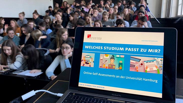 Das Bild zeigt Studierende in einem Hörsaal, denen das Angebot des OSA-Zentrums erläutert wird.